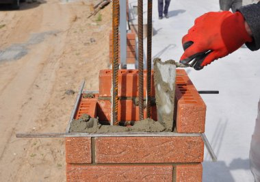 Closeup of a Bricklayer Worker Installing Red Blocks and Caulking Brick Masonry Joints Exterior Wall with Trowel Putty Knife Outdoor