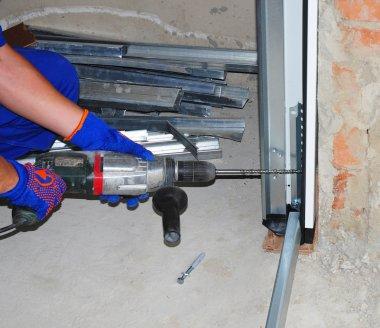 Repairman Installing Garage Door. Contractor Using Drill and Met