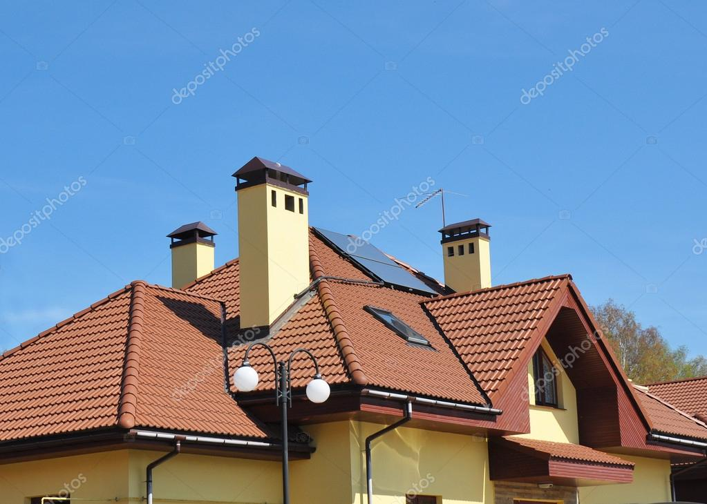 Closeup of solar panel on red tiled house roof