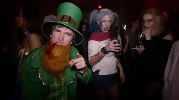 SAINT PETERSBURG, RUSSIA - OCTOBER 31, 2015: Man in leprechaun costume, woman with grey hair at Halloween party. Slow motion