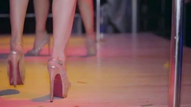 Dancing legs of go go dancer on high heels in nightclub. Red tippet. Slow motion