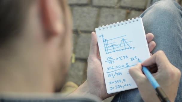 Muž ruka přitahuje matematické úkoly modrá značka na papírového poznámkového bloku, otočení stránky. Pohled shora