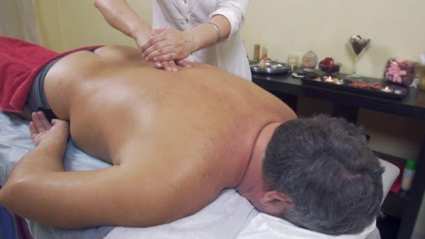 Masérka rukou stiskněte páteř dospělých tlustého muže. Nápravě masáž. Střední záběr