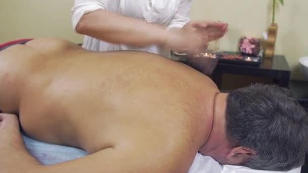 Masérka specialista klepnutím na zadní část dospělých tlusťoch. Léčivá masáž. Střední záběr