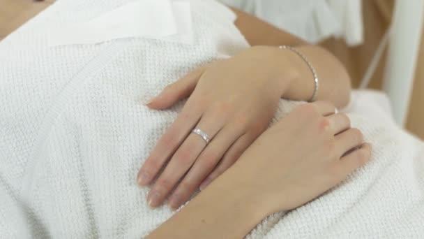 Zblízka kosmetička ruce aby epilace obličeje dívka v saloonu. Zarudnutí