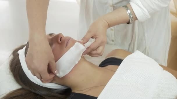 Close up of beautician hands make epilation of girl chin in professional saloon