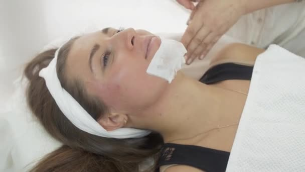 Close up of beautician hand make epilation of girl chin by wax strips in saloon