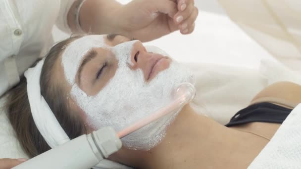 Close up darsonvalization girl face with mask in beauty saloon. Cosmetologist