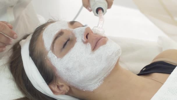 Close up darsonvalization girl face with clay mask in saloon. Cosmetic procedure.