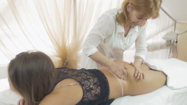 Masseuse make massage of gluteus to girl in thong, black top in beauty saloon