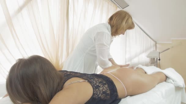 Masseuse make massage of right leg to girl in beauty saloon. Strong stroking