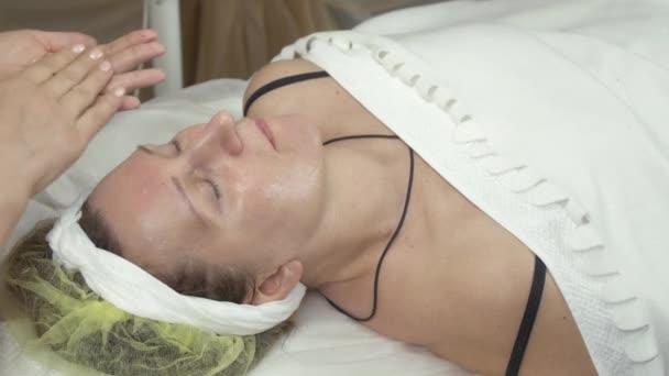 Kosmetikerin setzte im Schönheitssalon Feuchtigkeitscreme auf das Gesicht einer erwachsenen Frau.