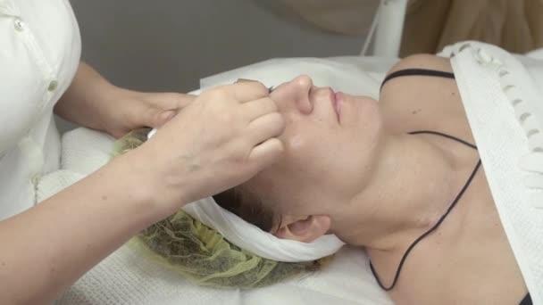 Kosmetolog se galvanotherapy tvář dospělé ženy v salónu krásy