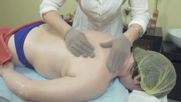 Masérka dělat léčení masáž zad tlustou ženu masážní rukavice v saloonu.