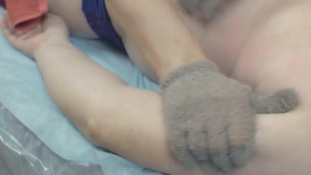 Masérka, aby léčivá masáž rukou tlustou ženu masážní rukavice v saloonu