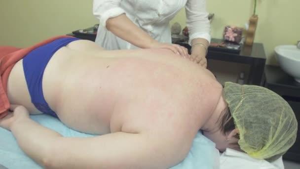 Masérka se nápravě masáž zad pro dospělé tlusté ženy v saloonu.