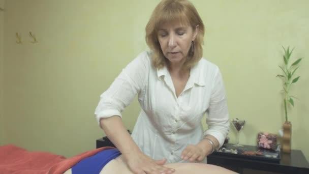 Masérka se nápravě masáž dolní části zad, ramen tlusté ženě v saloonu