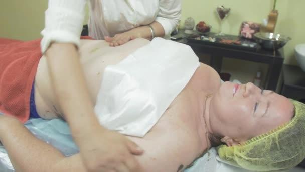 Kosmetolog masírovat žaludek tlusté ženy v salonu krásy. Zdravotní péče