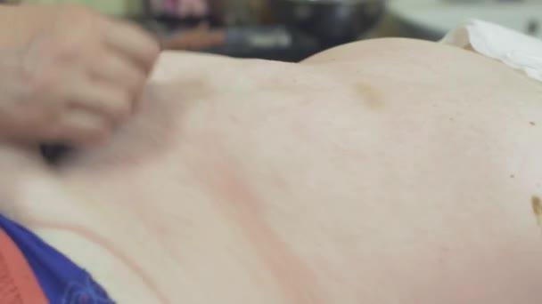 Masérka kamenné terapie masáž břicha tlustá žena v profesionálním salónu