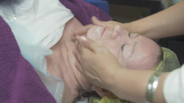 Cosmetologist smear moisturizing cream on thick woman face in beauty saloon.