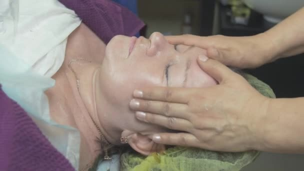 Cosmetologist make massage of area around eyes to thick woman in beauty saloon