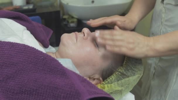 Cosmetologist make massage face to adult thick woman in beauty saloon. Stroking.
