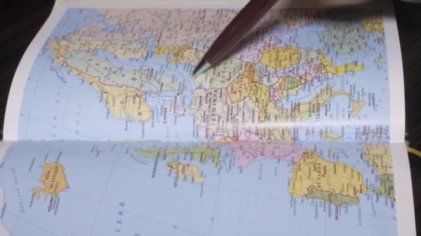 Right mans hand search Norway, Poland on paper geography map by a pen. Close up