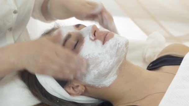 Close up cosmetologist hands rub in clay mask into girl face in beauty saloon