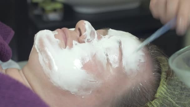 Cosmetologist put algae mask on face of thick woman in beauty saloon by spoon.