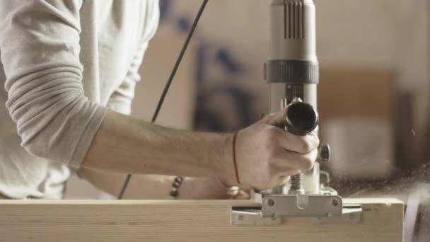 Tischler schnitt Holzbretter durch Tauchfräse. Möbel. Gerade Linie. Sägemehl