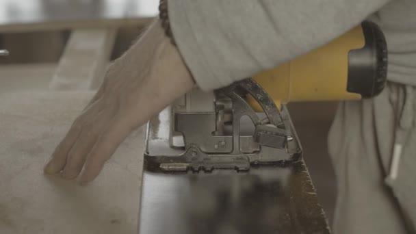Tvář tesaře řízl dřevěnou desku na rovné lince. Kotoučové pily