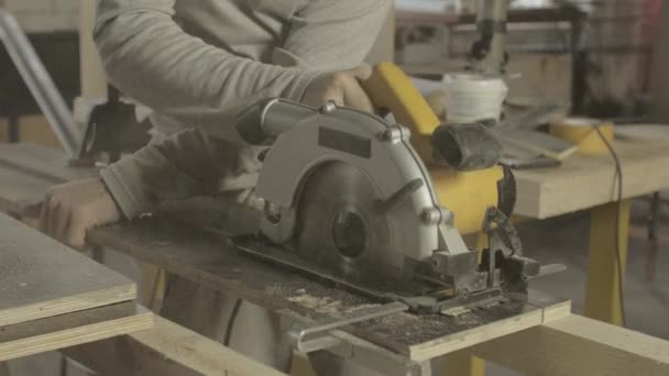 Carpenter cut wooden board on two parts by circular saw. Woodworker