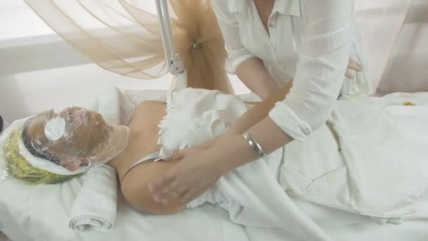 Masseuse make massage of right woman hand in beauty saloon. Thermo mask on face
