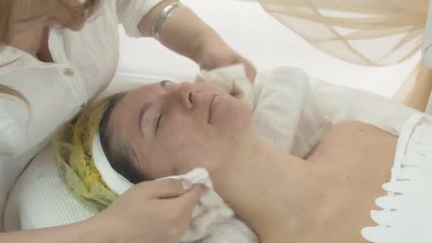 Female cosmetologist wipe out woman face and neck by napkins in beauty saloon.