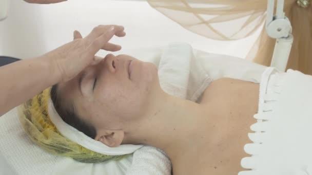 Cosmetologist smear bit moisturizing oil on woman face in beauty saloon.