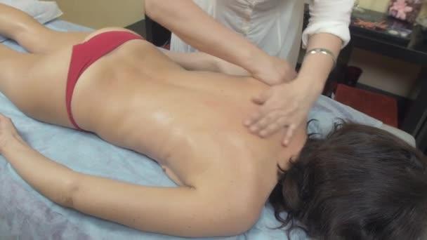 Masseuse machen Heilmassage von Rücken zu junge schlanke Frau im Salon. Streicheln