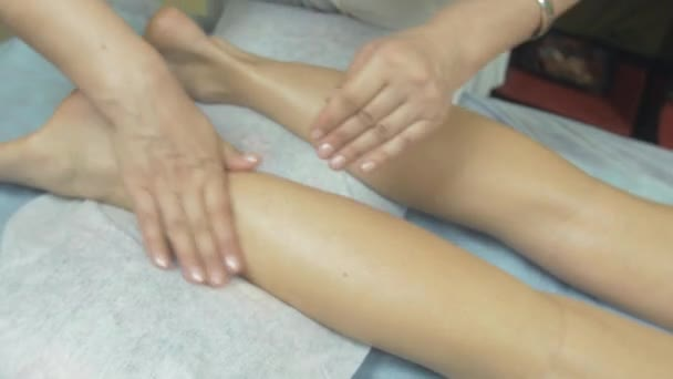Masseuse make healing massage of right leg to woman in professional saloon.