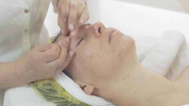 Cosmetologist make acupressure of eyebrows on woman face in beauty saloon.
