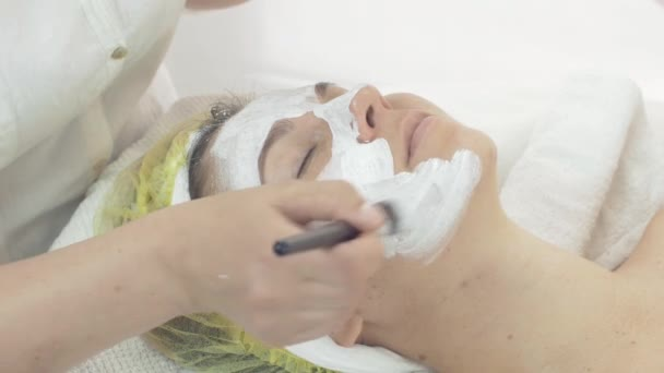 Cosmetologist put white clay mask on woman face by brush in beauty saloon