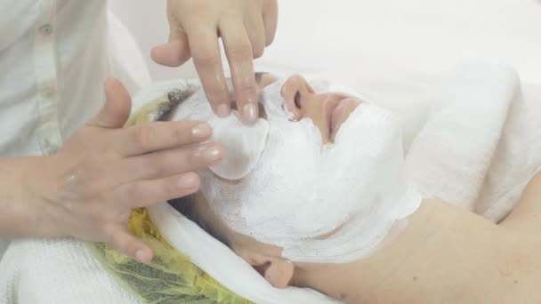 Cosmetologist put cotton pad on woman eyes, cover face by cheesecloth in saloon.