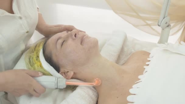 Cosmetologist make darsonvalization on woman face and neck in beauty saloon.