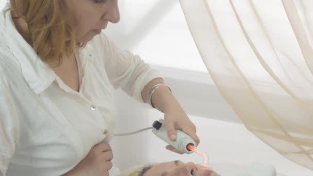 Cosmetologist use darsonval on woman face in beauty saloon. Regeneration of skin