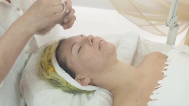 Cosmetologist put green clay mask on woman face in beauty saloon. Skincare
