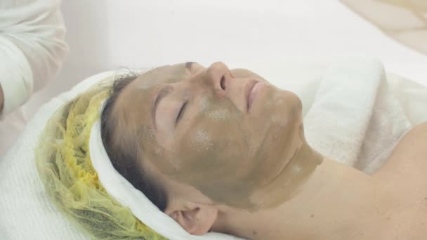 Woman face with green clay cosmetic mask in beauty saloon. Skincare. Cosmetology