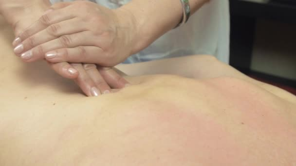 Masseuse make therapeutic massage of backbone to young woman in saloon.