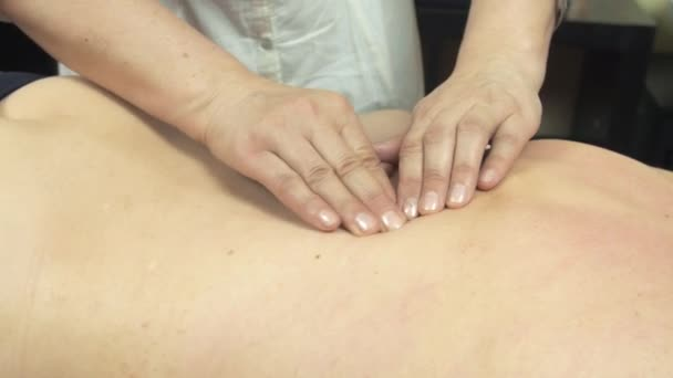 Masseuse make therapeutic massage of backbone to young woman in saloon. Pressing