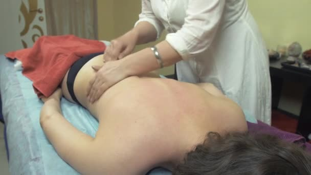 Masseuse make therapeutic massage of back, shoulders to young woman in saloon.