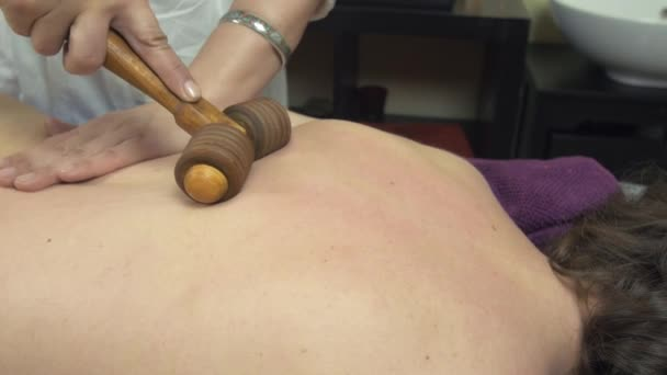 Masseuse make healing massage of backbone neck by wooden massage roller to woman