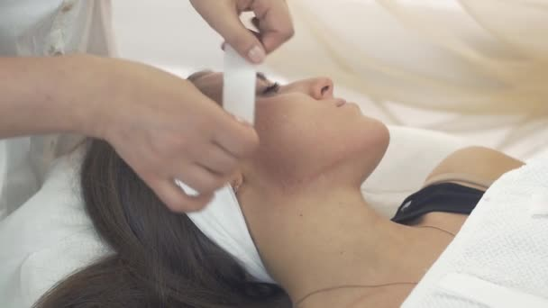 Cosmetologist remove waxing strip out cheeks of girl in beauty saloon. Epilation