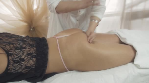 Masseuse make massage of gluteus against cellulitis to girl in saloon. Beating